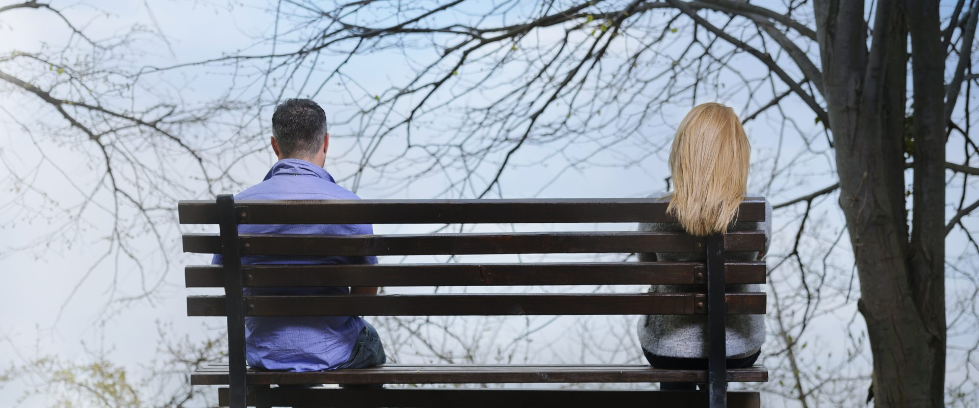 Rear view of couple with relationship difficulties sitting on bench.